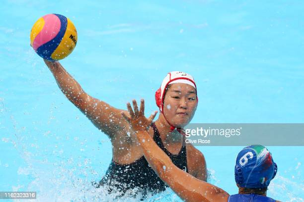 Yumi Arima of Japan takes a shot against Rosaria Aiello of Italy during their Women's Water Polo Preliminary round match on day four of the Gwangju...