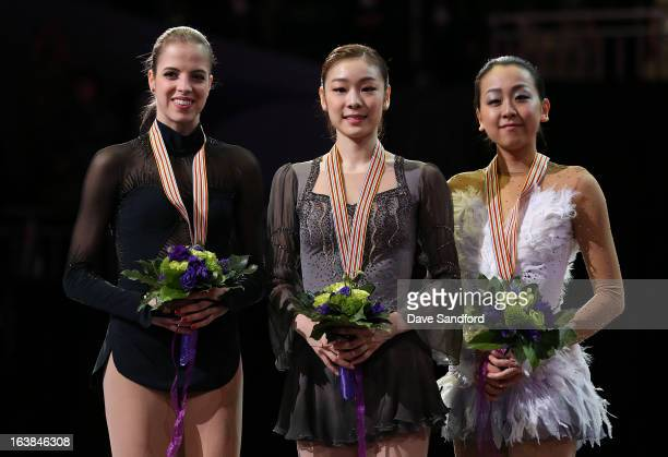 Yuna Kim of South Korea celebrates winning the gold medal with Carolina Kostner of Italy winning silver medal and Mao Asada of Japan winning the...