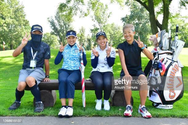 Yuna Takagi Mizuki Tanaka of Japan and their caddies pose for photographs during a practice round ahead of the Nitori Ladies Golf Tournament at the...