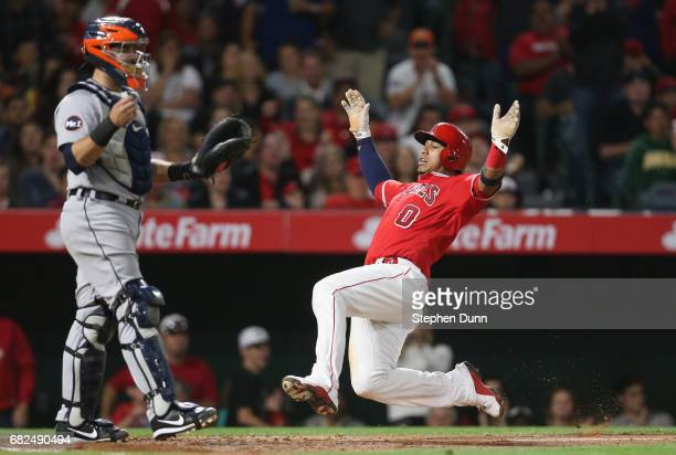 Yunel Escobar of the Los Angeles Angels of Anaheim slides home with a run in the sixth inning past catcher Alex Avila of the Detroit Tigers at Angel...