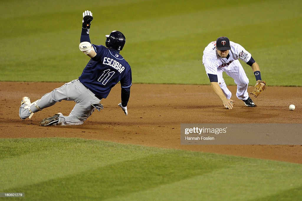 Yunel Escobar #11 of the Tampa Bay Rays slides safely into second base as Brian Dozier #2 of the Minnesota Twins is unable to hold onto the ball during the third inning of the game on September 13, 2013 at Target Field in Minneapolis, Minnesota.