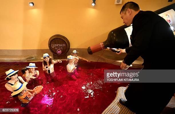 Yunessan sommelier Yasunari Kuwajima pours 2016 Beaujolais Nouveau wine into the wine spa of the Hakone Yunessun spa resort facilities in Hakone town...