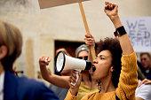 Yung black woman shouting through megaphone on anti-racism demonstrations.