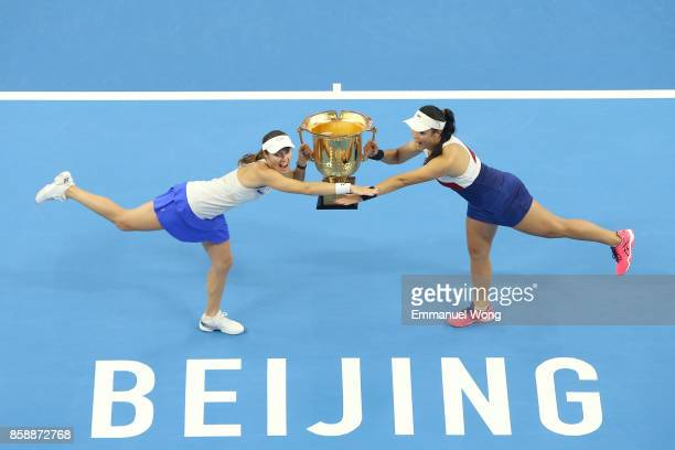 YungJan Chan of Chinese Taipei and Martina Hingis of Switzerland pose with their trophy after winning the Women's doubles final match against Timea...
