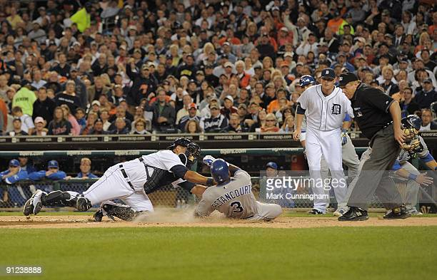Yuniesky Betancourt of the Kansas City Royals slides into home while Gerald Laird of the Detroit Tigers makes the tag as Eddie Bonine and homeplate...