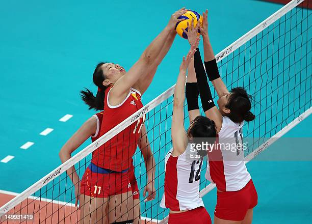 Yunli Xu of China tries to get the ball past Ai Otomo and Risa Shinnabe of Japan during Women's Volleyball on Day 11 of the London 2012 Olympic Games...