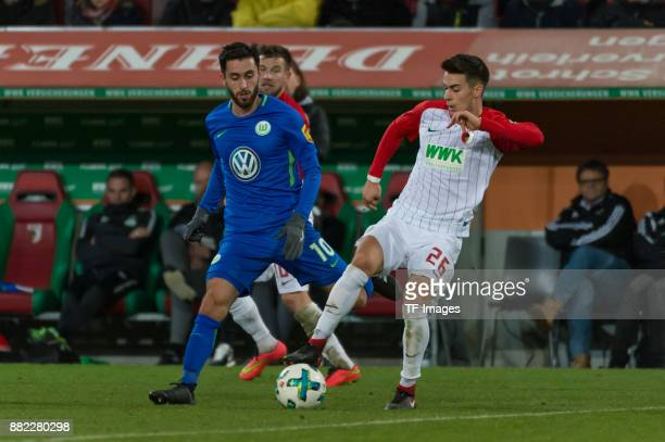 Yunus Malli of Wolfsburg and Erik Thommy of Augsburg battle for the ball during the Bundesliga match between FC Augsburg and VfL Wolfsburg at...