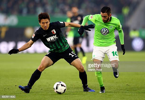 Yunus Malli of Wolfsburg and Ja Cheol Koo of Augsburg battle for the ball during the Bundesliga match between VfL Wolfsburg and FC Augsburg at...