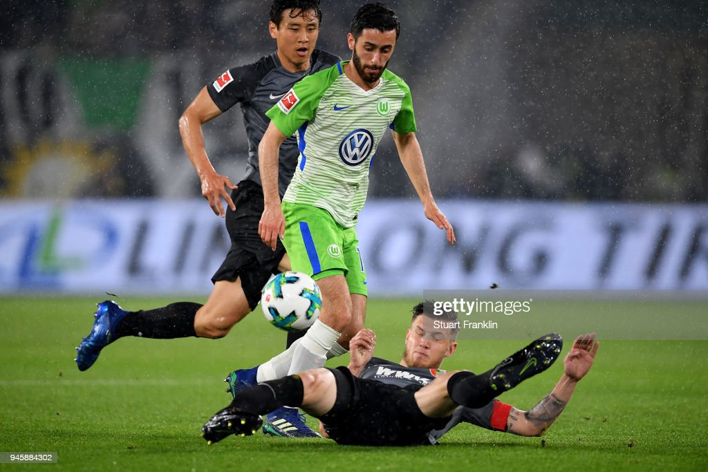 Yunus Malli (L) of Wolfsburg and Jeffrey Gouweleeuw of Augsburg battle for the ball during the Bundesliga match between VfL Wolfsburg and FC Augsburg at Volkswagen Arena on April 13, 2018 in Wolfsburg, Germany.