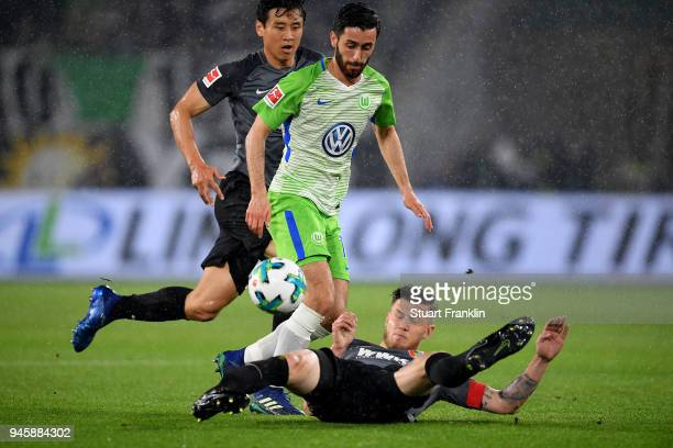 Yunus Malli of Wolfsburg and Jeffrey Gouweleeuw of Augsburg battle for the ball during the Bundesliga match between VfL Wolfsburg and FC Augsburg at...
