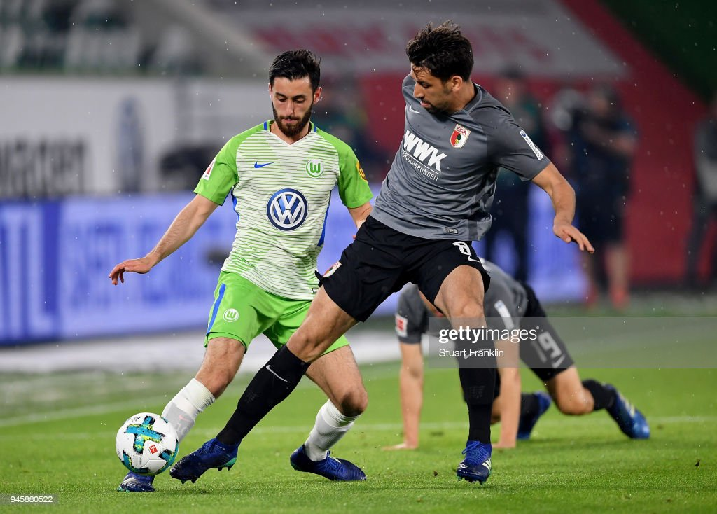 Yunus Malli (L) of Wolfsburg and Rani Khedira of Augsburg battle for the ball during the Bundesliga match between VfL Wolfsburg and FC Augsburg at Volkswagen Arena on April 13, 2018 in Wolfsburg, Germany.