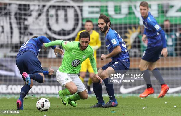 Yunus Malli of Wolfsburg is attacked by Markus Steinhoefer and Hamit Altintop of Darmstadt during the Bundesliga match between VfL Wolfsburg and SV...