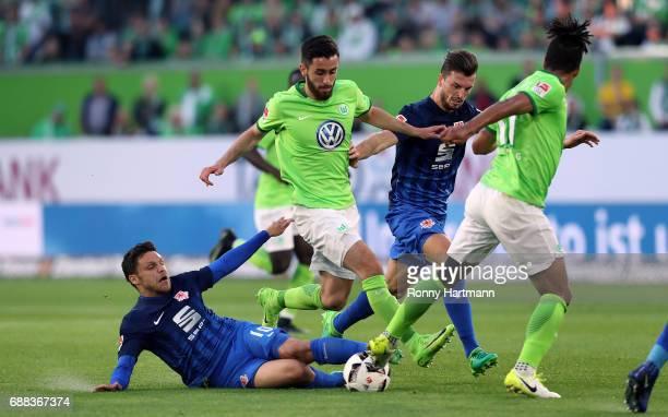 Yunus Malli of Wolfsburg is attacked by Mirko Boland and Gustav Valsvik of Braunschweig during the Bundesliga Playoff first leg match between VfL...