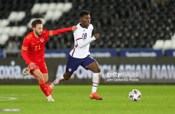 Yunus Musah of the United States runs past Josh Sheehan of Wales during a game between Wales and USMNT at Liberty Stadium on November 12, 2020 in...