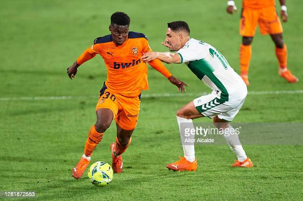 Yunus Musah of Valencia CF competes for the ball with Fidel Chaves of Elche CF during the La Liga Santander match between Elche CF and Valencia CF at...