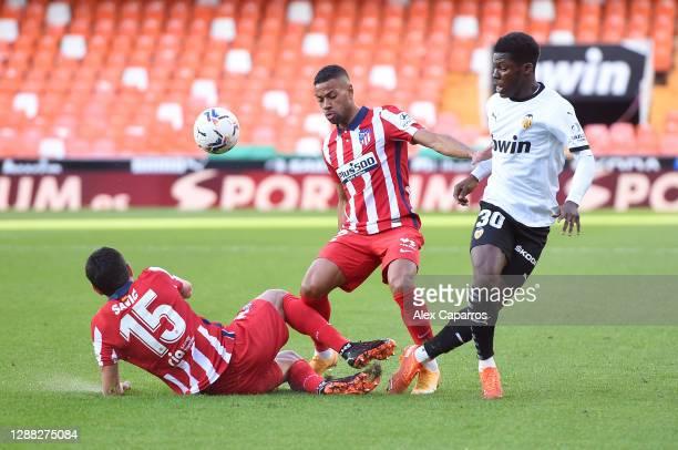 Yunus Musah of Valencia is challenged by Stefan Savic and Renan Lodi of Atletico de Madrid during the La Liga Santander match between Valencia CF and...
