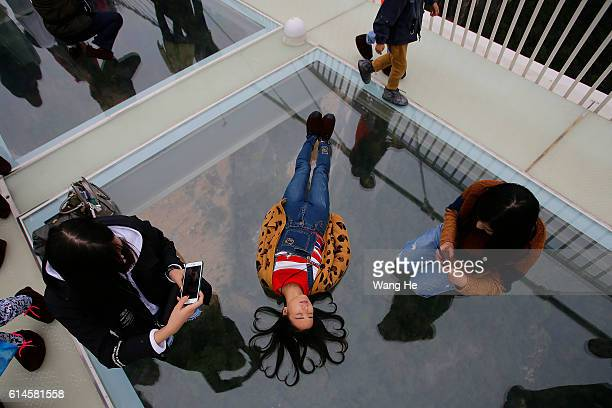 Yuong women pose for pictures on the glassfloor suspension bridge in Zhangjiajie in south China's Hunan province on October 14 2016 in Zhangjiajie...