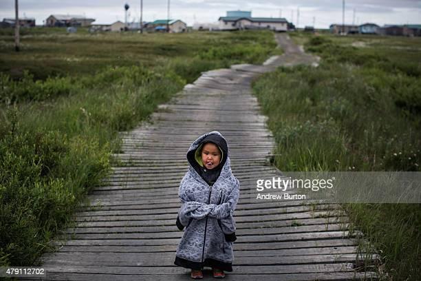 Yupik child stands on raised wooden sidewalks used to help cross unstable ground on June 30 2015 in Newtok Alaska Newtok which has a population of...