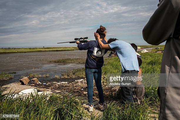 Yupik children shoot a rifle on July 3 2015 in Newtok Alaska Newtok is one of several remote Alaskan villages that is being forced to relocate due to...