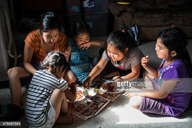 Yupik family eats a meal of salmon that is half dried then smoked and boiled on July 3 2015 in Newtok Alaska Newtok is one of several remote Alaskan...