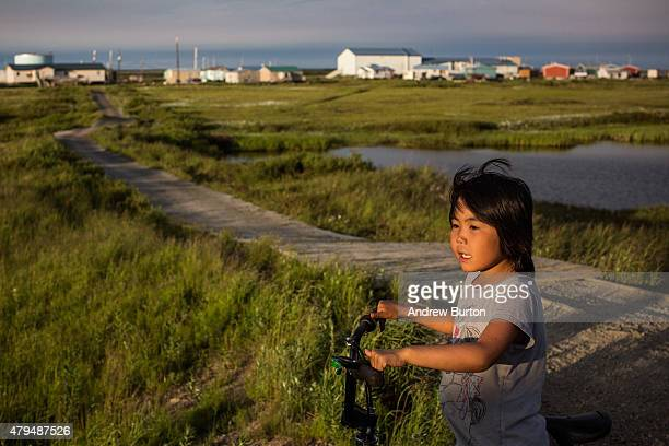 Yupik girl rides her bike late in the evening on July 3 2015 in Newtok Alaska Newtok is one of several remote Alaskan villages that is being forced...