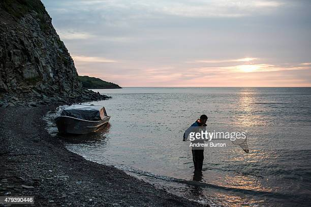 Yupik man fishes with nets while waiting for the tide to come in after a day of salmon fishing on July 1 2015 in Newtok Alaska Newtok has a...