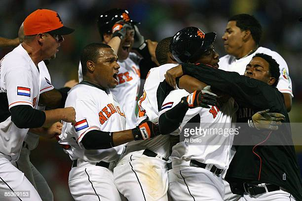 Yurendell de Caster of the Netherlands is mobbed by his teammates after driving in the the winning run on an error by Willy Aybar of the Dominican...