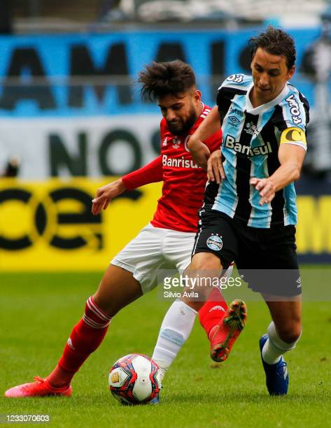 Yuri Alberto of Internacional and Pedro Geromel of Gremio fight for the ball during the final of Rio Grande Do Sul State Championship 2021 between...