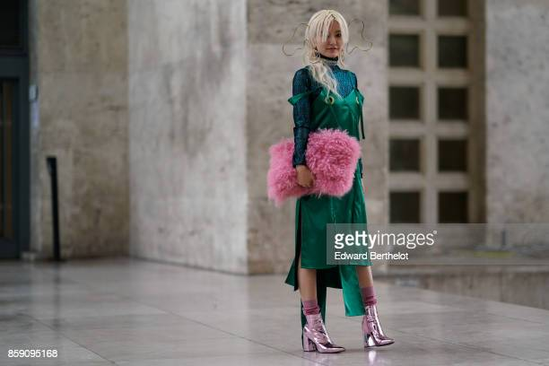 Yuri Nakagawa wears a pink fluffy bag a green dress pink shiny shoes outside Andrew GN during Paris Fashion Week Womenswear Spring/Summer 2018 on...