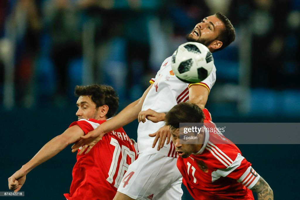 Yuri Zhirkov (L) and Fedor Smolov (R) of Russia vie for the ball with Nacho of Spain during Russia and Spain International friendly match on November 14, 2017 at Saint Petersburg Stadium in Saint Petersburg, Russia.