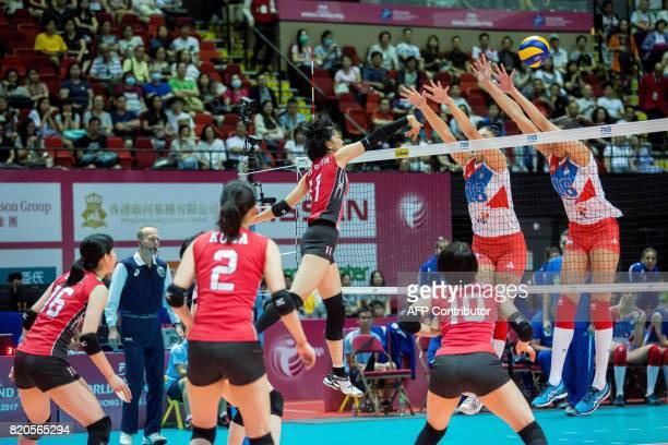 Yurie Nabeya of Japan spikes the ball past the defence of Milena Rasic and Tijana Boskovic of Serbia during their match at the Women's Volleyball...