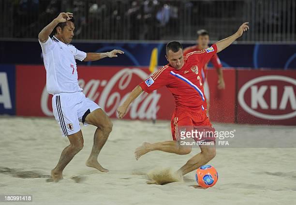 Yury Gorchinskiy of Russia shoots as Takeshi Kawaharazuka of Japan looks on during the FIFA Beach Soccer World Cup Tahiti 2013 Group D match between...