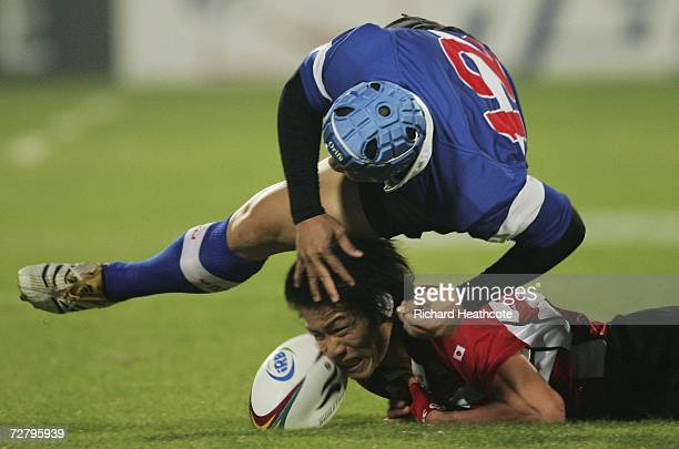 Yusaku Kuwazuru of Japan is tackled by Huang Han Yang of Chinese Taipei during the Rugby 7's Semi Final match during the 15th Asian Games Doha 2006...