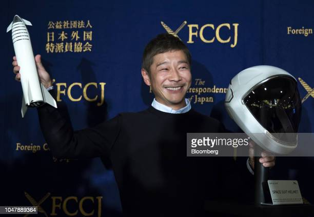Yusaku Maezawa chief executive officer of Zozo Inc poses with a model of the SpaceX BFR rocket and the spacesuit's helmet during a news conference at...