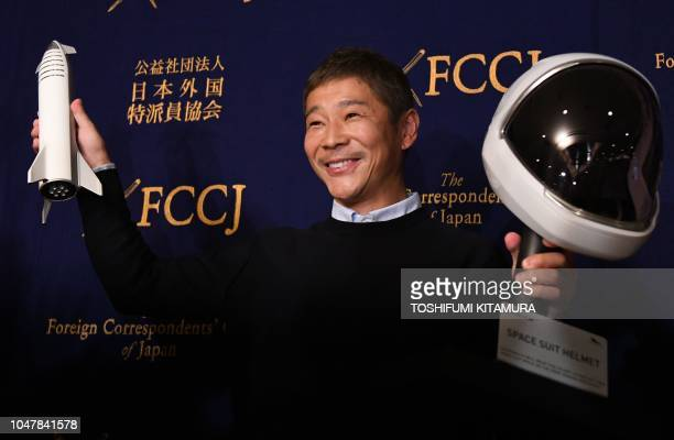 Yusaku Maezawa entrepreneur and CEO of ZOZOTOWN and SpaceX BFR's first private passenger poses with a miniature rocket and space helmet prior to...