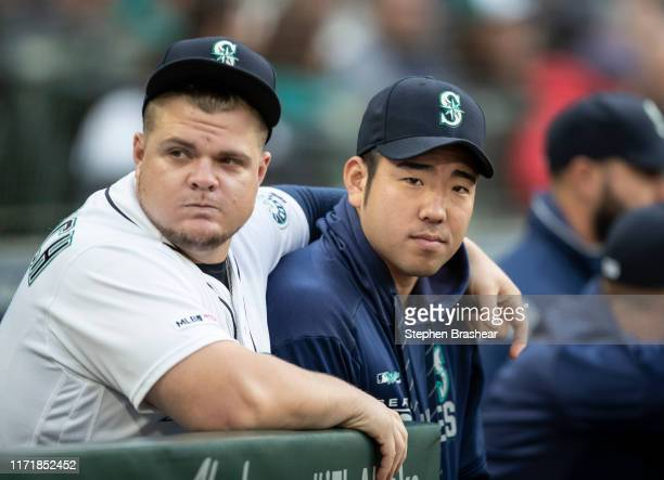 Yusei Kikuchi of the Seattle Mariners stands next to Daniel Vogelbach at the top of the dugout brefore a game against the Oakland Athletics at...