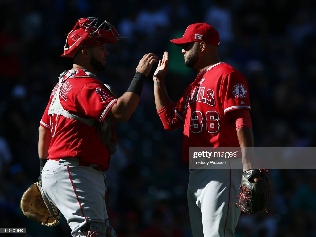 Yusmeiro Petit #36 of the Los Angeles Angels of Anaheim, right, is greeted by Martin Maldonado #12 after securing the win against the Seattle Mariners at Safeco Field on September 10, 2017 in Seattle, Washington.