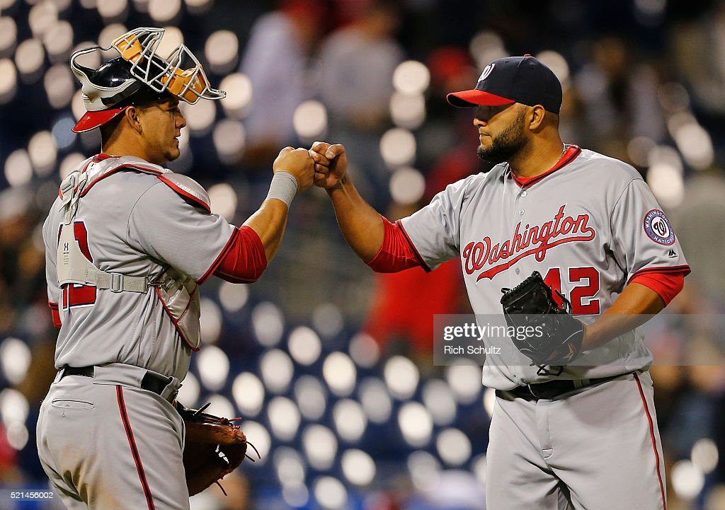 Yusmeiro Petit , right, of the Washington Nationals is congratulated by catcher Wilson Ramos, left, after they beat the Philadelphia Phillies 9-1 in an MLB game at Citizens Bank Park on April 15, 2016 in Philadelphia, Pennsylvania. All players are wearing #42 in honor of Jackie Robinson.
