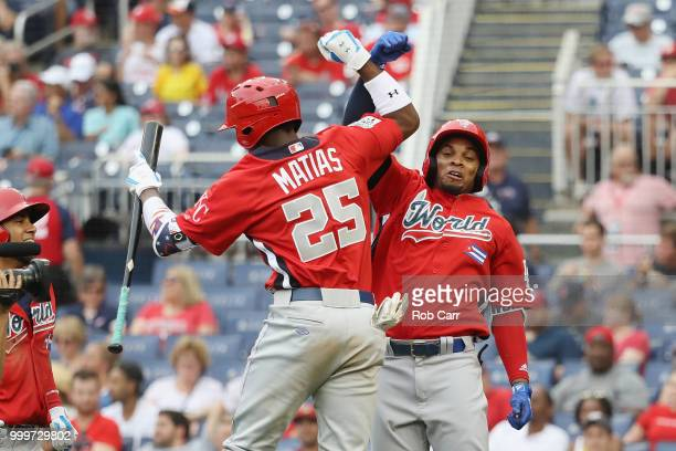 Yusniel Diaz of the Los Angeles Dodgers and the World Team celebrates with teammate Seuly Matias of the Kansas City Royals and the World Team after...