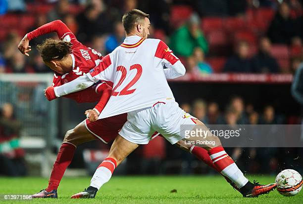 Yussuf Poulsen of Denmark and Marko Simic of Montenegro compete for the ball during the FIFA World Cup 2018 european qualifier match between Denmark...