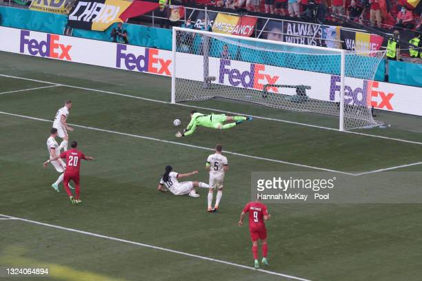 Yussuf Poulsen of Denmark scores their side's first goal past Thibaut Courtois of Belgium during the UEFA Euro 2020 Championship Group B match...
