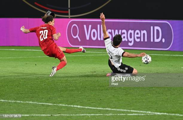 Yussuf Poulsen of Denmark scores their side's first goal whilst under pressure from Mats Hummels of Germany during the international friendly match...