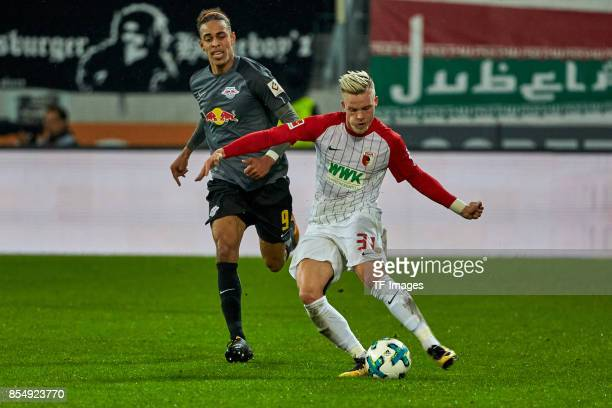 Yussuf Poulsen of Leipzig and Philipp Max of Augsburg battle for the ball during the Bundesliga match between FC Augsburg and RB Leipzig at WWKArena...