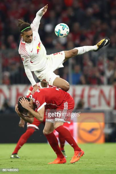 Yussuf Poulsen of Leipzig fights for the all with Javi Martinez of Bayern Muenchen during the Bundesliga match between FC Bayern Muenchen and RB...