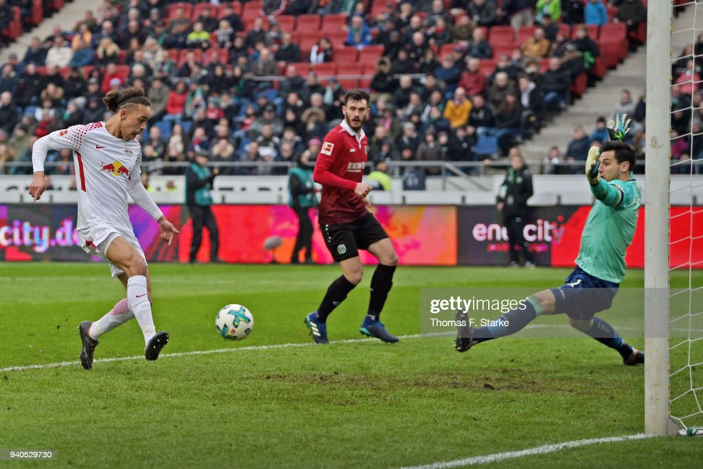Yussuf Poulsen (L) of Leipzig scores against goalkeeper Philipp Tschauner (R) of Hannover during the Bundesliga match between Hannover 96 and RB Leipzig at HDI-Arena on March 31, 2018 in Hanover, Germany.