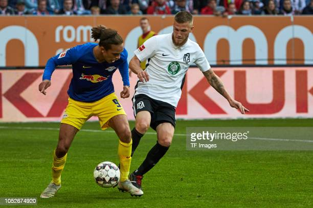 Yussuf Poulsen of RB Leipzig and Jeffrey Gouweleeuw of FC Augsburg battle for the ball during the Bundesliga match between FC Augsburg and RB Leipzig...