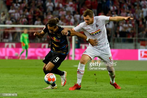 Yussuf Poulsen of RB Leipzig and Luca Kilian of 1. FC Koeln battle for the ball during the Bundesliga match between 1. FC Koeln and RB Leipzig at...