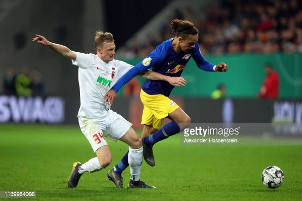 Yussuf Poulsen of RB Leipzig avoids a tackle from Philipp Max of FC Augsburg during the DFB Cup match between FC Augsburg and RB Leipzig at WWKArena...