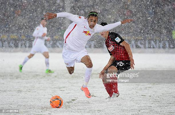 Yussuf Poulsen of RB Leipzig is challenged by MarcOliver Kempf of Freiburg during the Second Bundesliga match between SC Freiburg and RB Leipzig at...