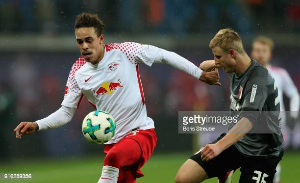 Yussuf Poulsen of RB Leipzig is challenged by Martin Hinteregger of FC Augsburg during the Bundesliga match between RB Leipzig and FC Augsburg at Red...